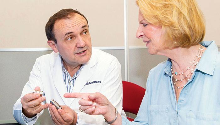 Dr. Radu explains the benefits of dental implants to a patient.