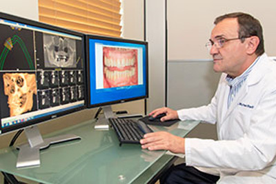 Dr. Radu plans the dental implant placement procedure using 3D X-rays and computer design software.