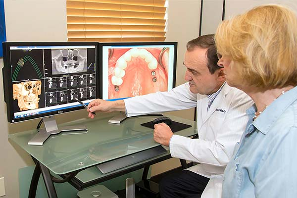 Dentist showing patient 3D X-rays