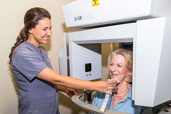 Dental assistant taking 3D X-rays of a patient