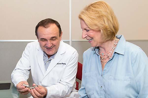 Dentist showing patient a dental implant