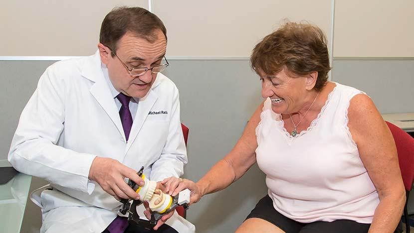 Dentist showing patient model of dentures