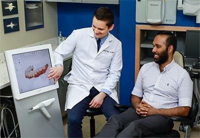 Dentist showing patient 3D scanner