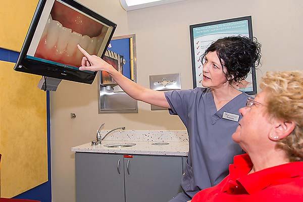 Hygienist showing patient intraoral photos