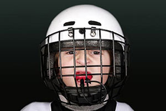 Child in football helmet with mouthguard